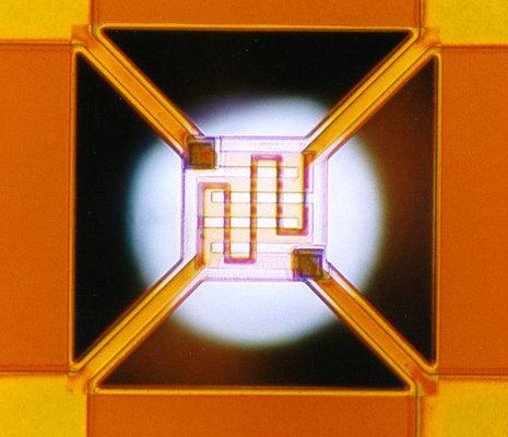Mikro pellisztor g�z�rz�kel�. A k�z�ps� n�gyzet m�rete 0.1 mm. Az als� spir�l a f�t�-, a fels� az �rz�kel� elektr�da.