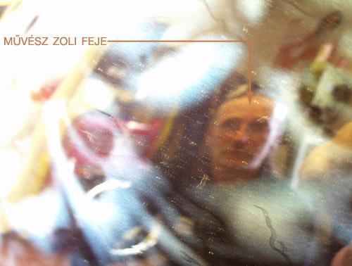 Művész Zoli feje az egyik munkáján tükröződve