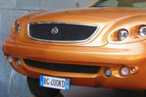 Narancssárga, gepárdszerű autó logója a torinói autómúzeum bejárata előtt 2003 májusában. Fotó: Kari