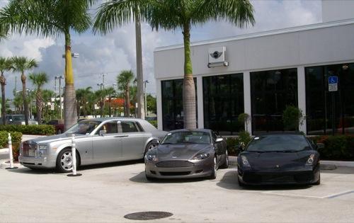 Rolls-Royce Phantom, Aston Martin DB9 és Lamborghini Gallardo egy autókereskedés parkolójában, hülyén beállva