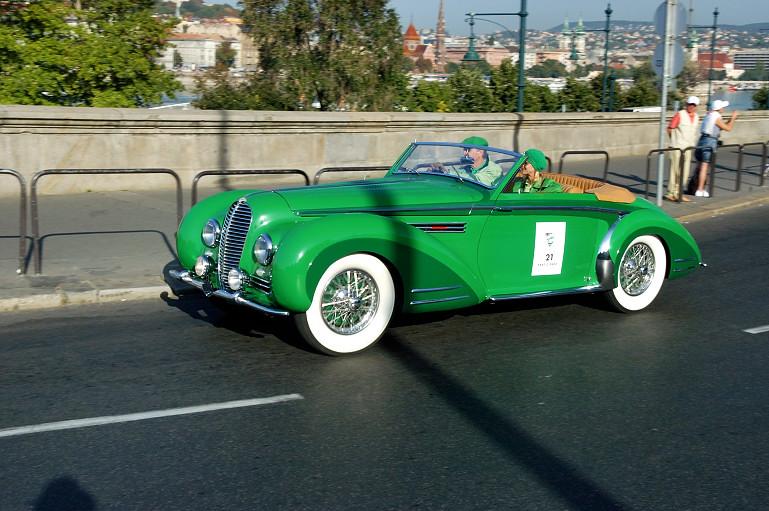 Figyeljük meg, ahogy a sapkák és a hölgy bőrkabátjának zöldje harmonizál az autóval. Nem véletlen. (Delahaye 135 MS 1947)