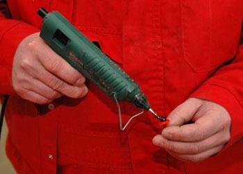 A tappancsokat meleg ragasztóval erősítik a lakkozott felületre...