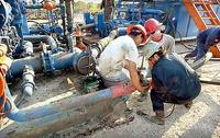 Drillers employed by Dewbre Petroleum attach piping to one of the two huge mud pumps at the site of an old oil well being prepared to work again in West George, Texas.